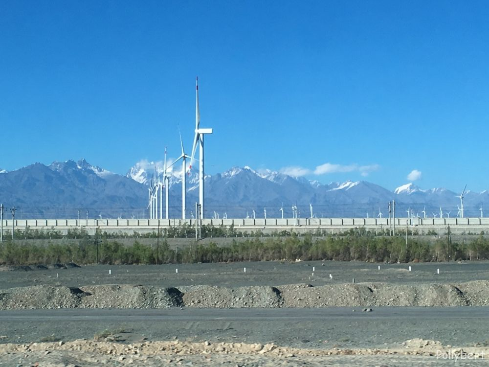 snow-capped mountains with wind turbine